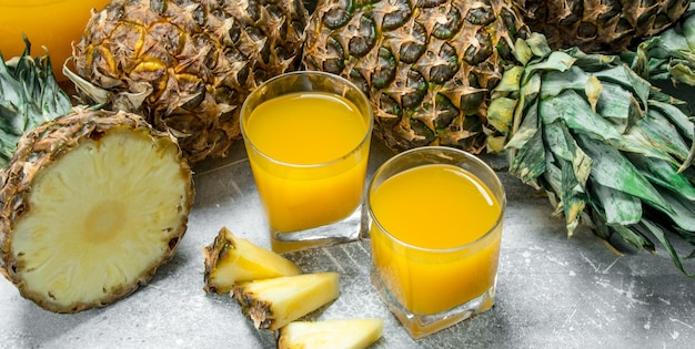 Świeży sok ananasowy i dojrzałe ananasy.