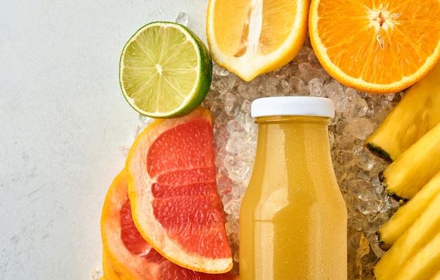 Świeży sok ananasowy na szklanym słoju z lodem i różnymi plastrami dojrzałych kolorowych owoców tropikalnych grejpfrut, pomarańcza, limonka, cytryna, kompozycja płasko leżąca, na jasnoszarej kamiennej powierzchni.