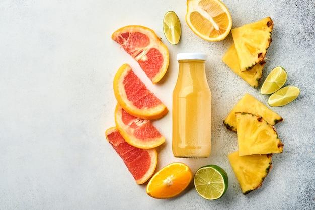 Świeży sok ananasowy na szklanym słoju z pokrojonymi w lód dojrzałymi owocami tropikalnymi grejpfrut, pomarańcza, limonka,