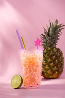 Świeży sok ananasowy w kieliszku koktajlowym przeciwko owocom ananasa i różowym tle. witam, transparent koncepcja lato.