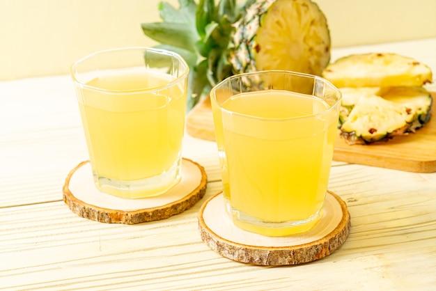 Świeży sok ananasowy w szklankach i ananasach na powierzchni drewna