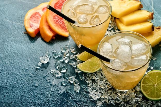 Świeży sok ananasowy z lodem i odmianą pokrojony w plasterki dojrzałych owoców tropikalnych koloru grejpfruta, pomarańczy, limonki, cytryny, płasko świecki skład, na ciemnym niebieskim tle kamienia.