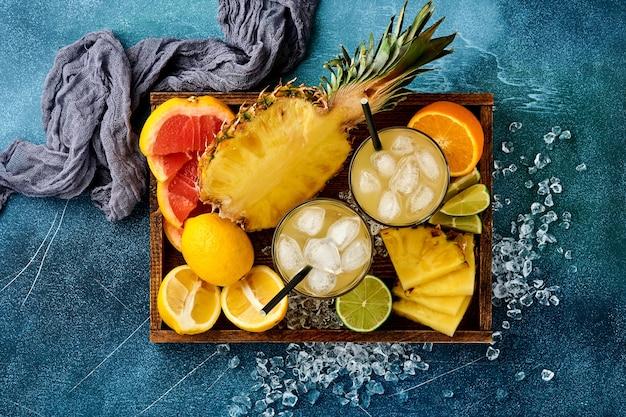 Świeży sok ananasowy z lodem i plastrami dojrzałych kolorowych owoców tropikalnych grejpfrut, pomarańcza, limonka,