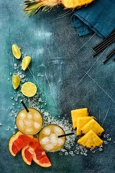 Świeży Sok Ananasowy Z Lodem I Plastrami Dojrzałych Kolorowych Owoców Tropikalnych Grejpfrut, Pomarańcza, Limonka, Premium Zdjęcia