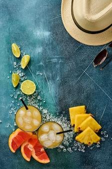 Świeży sok ananasowy z lodem i różnorodnymi plasterkami dojrzałych owoców tropikalnych w kolorze grejpfruta, pomarańczy, limonki, cytryny, słomkowy kapelusz plażowy i okulary przeciwsłoneczne, kompozycja płaska, na ciemnoniebieskim tle kamienia