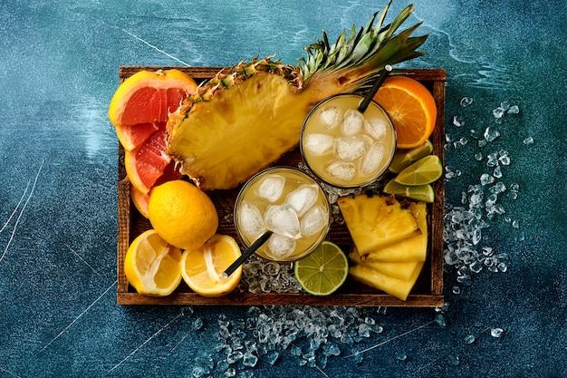 Świeży sok ananasowy z lodem i różnorodnymi plastrami dojrzałych kolorowych owoców tropikalnych grejpfrut, pomarańcza, limonka, cytryna, kompozycja flat lay, na ciemnoniebieskiej kamiennej powierzchni.