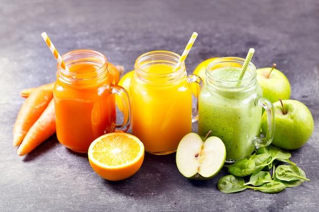Świeży sok i koktajle z owocami i warzywami na ciemnym stole