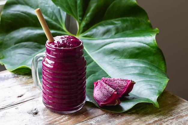 Świeży sok koktajlowy z owocu smoka (pitahaya) w szklanym słoju, plasterki owoców, tropikalny zielony liść na starym rustykalnym stole.