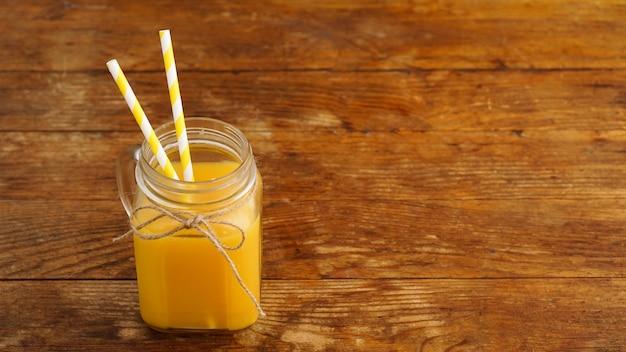 Świeży sok pomarańczowy na drewnianym stole. szklany słoik z dwiema papierowymi słomkami