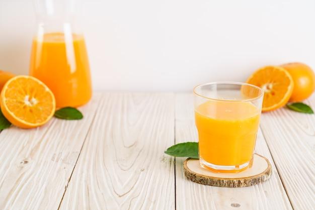 Świeży sok pomarańczowy na tle drewna