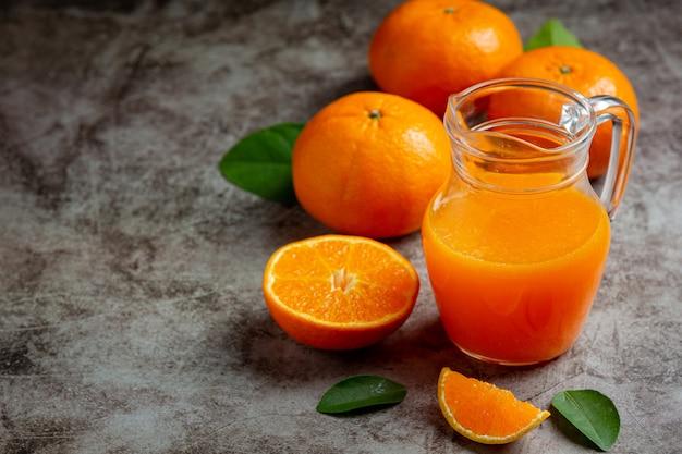 Świeży sok pomarańczowy w szklance na ciemnym tle