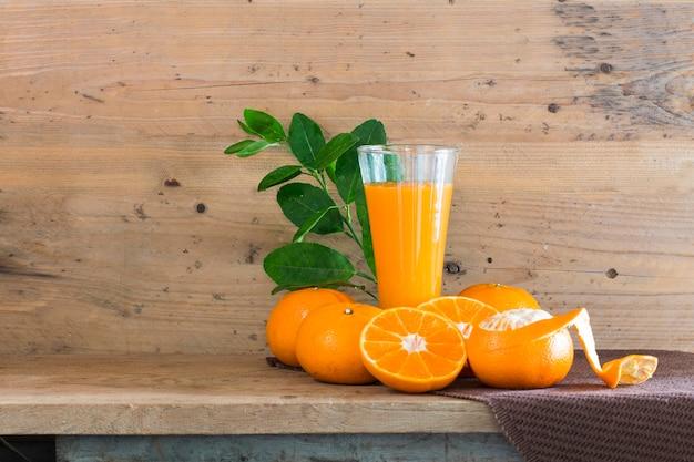 Świeży sok pomarańczowy w szkle na drewnie.