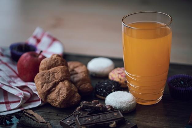 Świeży sok pomarańczowy w szkle z różnymi ciasteczkami