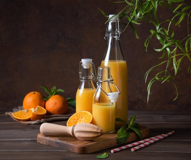 Świeży sok pomarańczowy w trzech butelkach z owocami cytrusowymi na desce do krojenia o brązowym drewnianym tle
