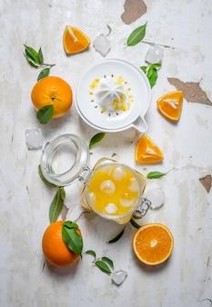 Świeży sok pomarańczowy z lodem, z kawałkami pomarańczy i sokowirówką
