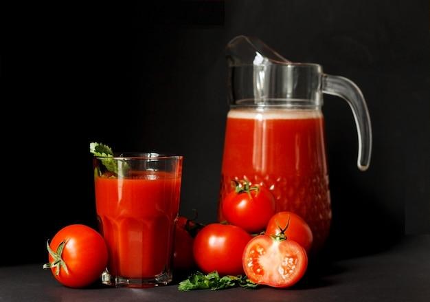 Świeży sok pomidorowy w szklance z pomidorami na ciemnym tle