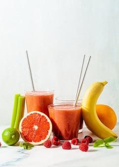 Świeży sok smoothie w szklankach z metalowymi rurkami na stole i składnikami.