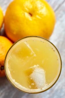 Świeży sok w szklance z lodem na stole i pomarańczami