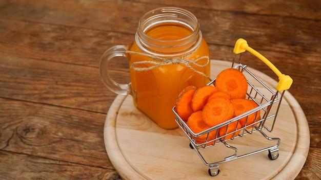 Świeży sok z marchwi z wózkiem supermarketu i na drewnianym tle. sok w szklanym słoju, domowy napój