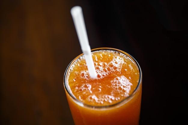 Świeży sok z papai w okrągłym szkle z rurką