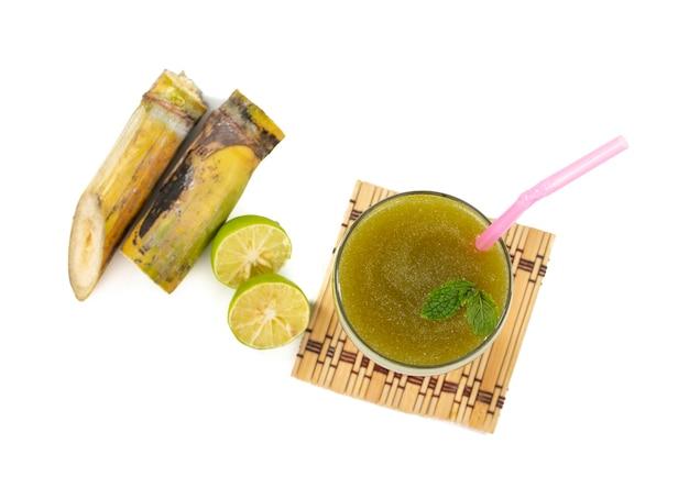 Świeży sok z trzciny cukrowej w szkle z kawałkami trzciny na izolowanej powierzchni