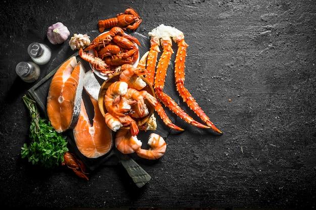 Świeży stek rybny na desce do krojenia z gotowanymi krewetkami, rakami i kraba.