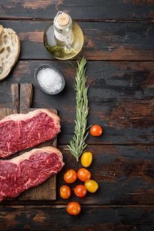 Świeży stek wołowy bez kości, surowy, na ciemnym drewnianym stole, widok z góry,