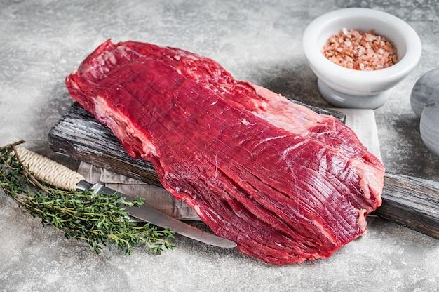Świeży stek wołowy lub klapa na desce z ziołami. szare tło. widok z góry.
