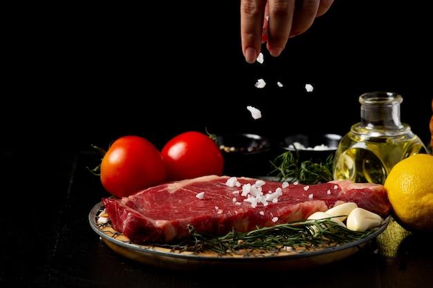 Świeży stek wołowy surowego na ciemnej powierzchni.