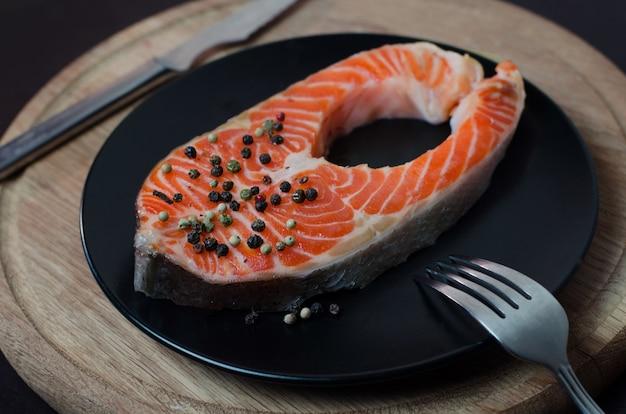 Świeży stek z łososia na czarnym talerzu