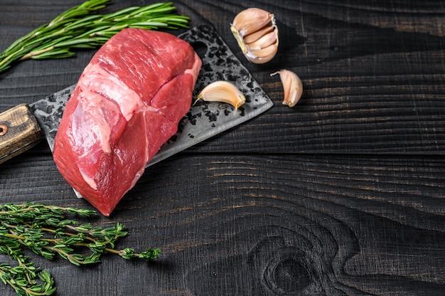 Świeży stek z mięsa cielęcego posiekać na tasak do mięsa. czarne drewniane tło. widok z góry. skopiuj miejsce.