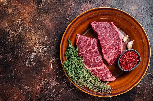 Świeży stek z surowego denveru lub mięsa z górnym ostrzem na rustykalnym talerzu z tymiankiem. ciemne tło. widok z góry. skopiuj miejsce.