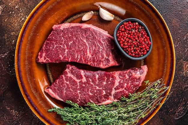Świeży stek z surowego denveru lub mięsa z górnym ostrzem na rustykalnym talerzu z tymiankiem. ciemne tło. widok z góry.
