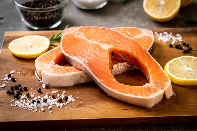 Świeży stek z surowego łososia ze składnikiem na pokładzie