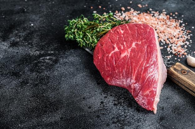 Świeży stek z surowego rumsztyku lub polędwicy wołowej na tasaku rzeźniczym. widok z góry.