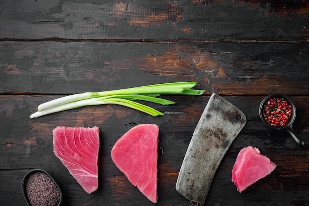 Świeży stek z surowego tuńczyka z zielonym groszkiem, sezamem i dymką oraz starym nożem tasakowym, na starym ciemnym drewnianym stole
