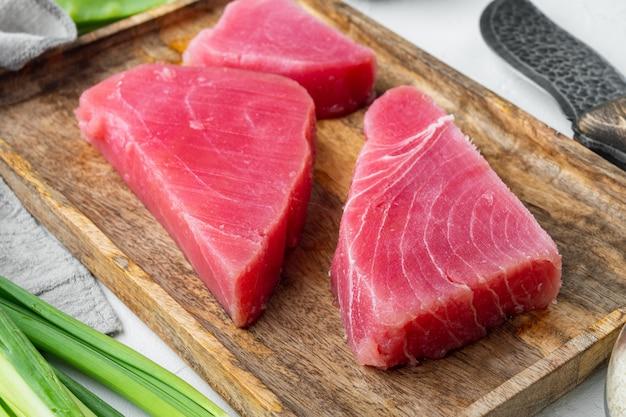 Świeży stek z surowego tuńczyka z zielonym groszkiem, sezamem i dymką ustawiony na drewnianej tacy, na białym kamieniu