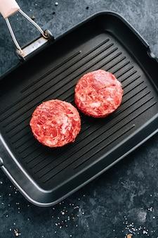 Świeży stek z surowej mielonej wołowiny do burgerów na czarnej patelni grillowej