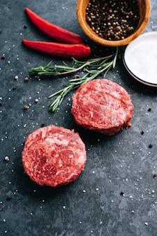 Świeży stek z surowej mielonej wołowiny do hamburgerów na czarnym tle z rozmarynem papryczką chili i przyprawami