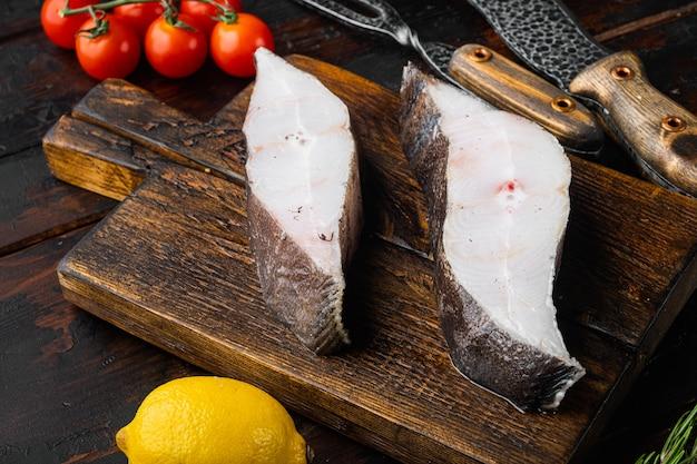 Świeży stek z surowej ryby halibuta, ze składnikami i ziołami rozmarynowymi, na starym ciemnym drewnianym stole tle