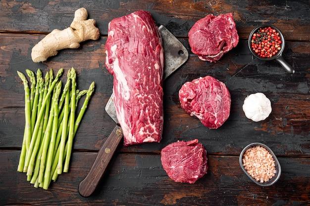 Świeży stek z surowej wołowiny mignon, z solą, pieprzem, tymiankiem, czosnkiem gotowy do zestawu, na starym ciemnym drewnianym stole tło, widok z góry płasko leżał
