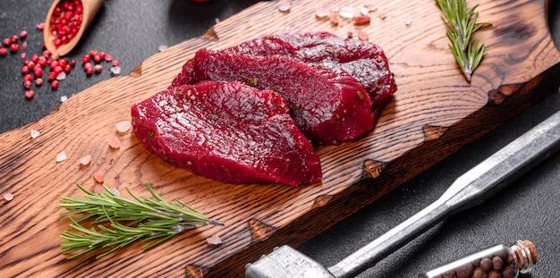 Świeży stek z surowej wołowiny mignon, z solą, pieprzem, tymiankiem, pomidorami. surowe świeże mięso marmurkowe stek i przyprawy