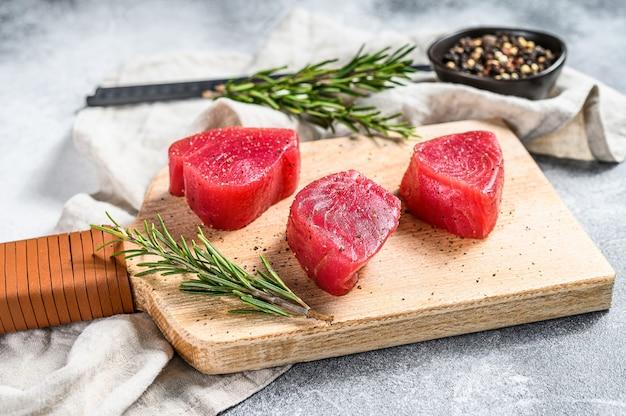 Świeży stek z tuńczyka na desce do krojenia. szare tło. widok z góry