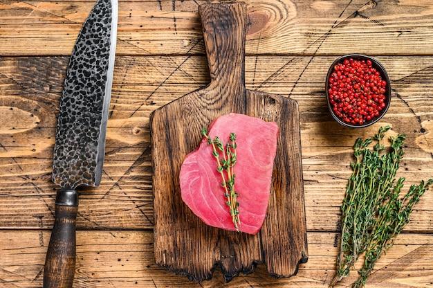 Świeży stek z tuńczyka surowego na drewnianą deskę do krojenia z nożem. drewniane tła. widok z góry.
