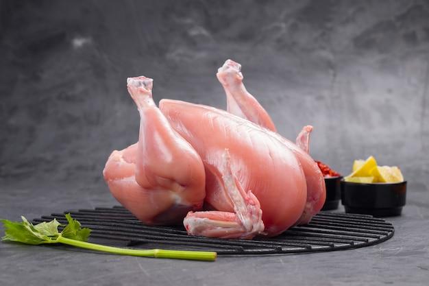 Świeży surowy cały kurczak umieszczony na grillu