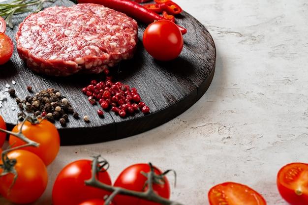 Świeży surowy domowy kotlet z przyprawami i pomidorami na stole