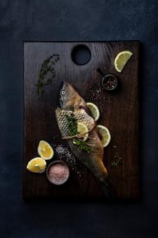 Świeży, surowy dziki karp z cytryną, solą morską i pieprzem