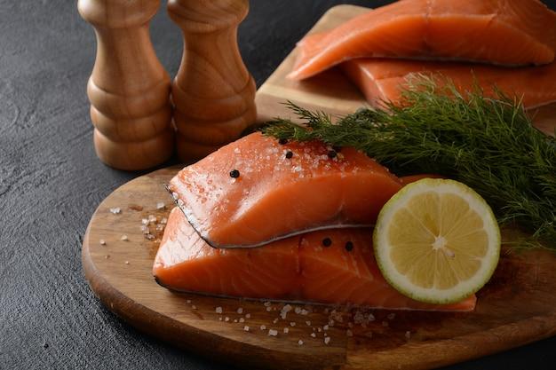 Świeży surowy filet z łososia z ziołami i cytryną na czarnym tle
