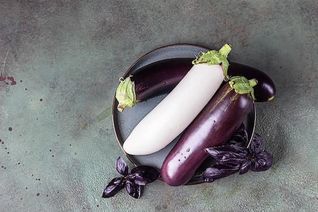 Świeży, surowy, fioletowy i biały bakłażan na talerzu ceramicznym z fioletową bazylią. widok z góry, miejsce na kopię.