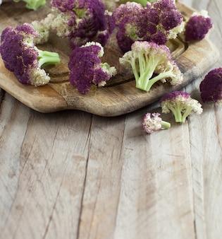 Świeży surowy fioletowy kalafior na drewnianej desce z bliska